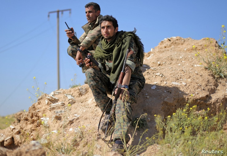 Fighters from the Syrian Democratic Forces hold walkie-talkies in the village of Baghuz, Deir el-Zour province, Syria, March 20, 2019.