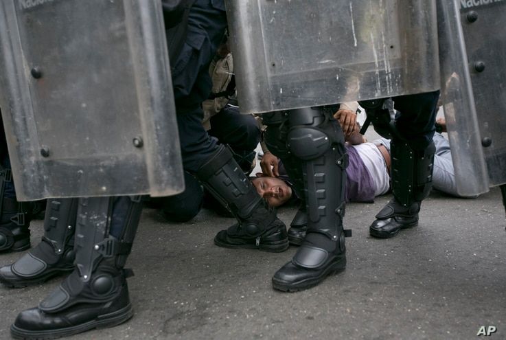 FILE - An anti-government protester is detained by Bolivarian National Police blocking protesters from reaching the headquarters of the national electoral body, CNE, to demand a recall referendum against President Nicolas Maduro in Caracas, Venezuela...