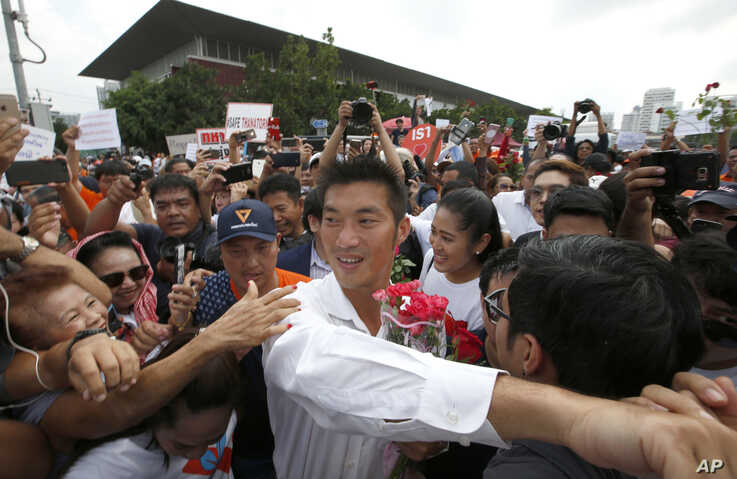Thailand's Future Forward Party leader Thanathorn Juangroongruangkit, center, is mobbed by his supporters upon arrival at a police station Bangkok, Thailand, April 6, 2019.