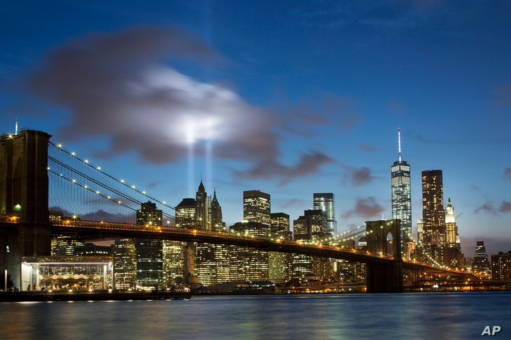 In this Sept. 10, 2014 file photo, the Tribute in Light rises behind the Brooklyn Bridge and buildings adjacent to the World Trade Center complex in New York.