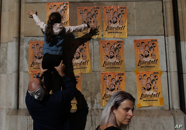 """A girl pastes a banner on a wall that reads in Catalan: """"Freedom for the Political Prisoners"""", during a protest against the decision of a judge to jail ex-members of the Catalan government at the University square in Barcelona, Spain,Nov. 5, 2017."""