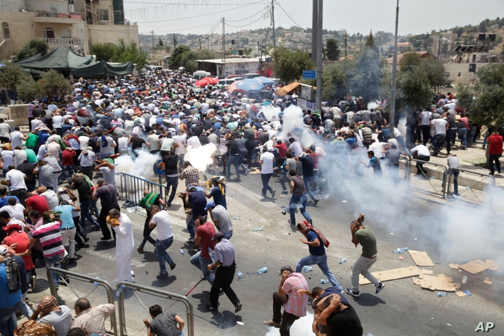 Palestinians run from tear gas thrown by Israeli police officers outside Jerusalem's Old City, July 21, 2017. Israel police severely restricted Muslim access to a contested shrine in Jerusalem's Old City  Friday to prevent protests over the installat...