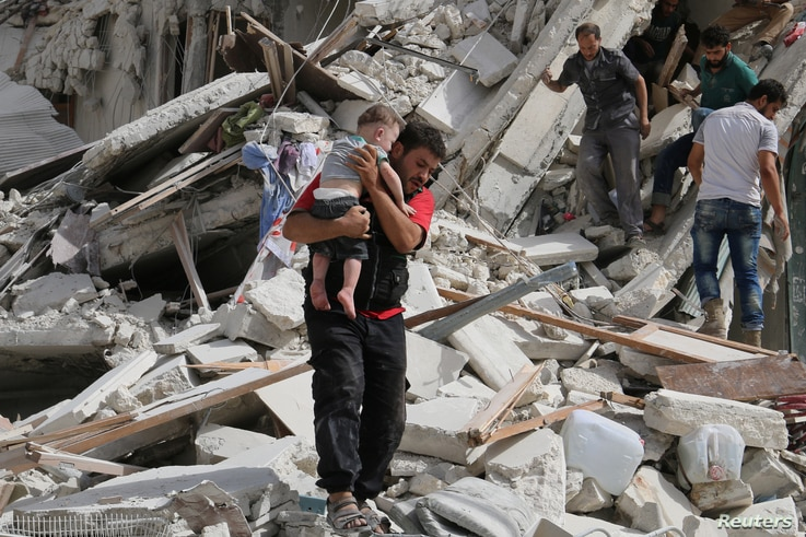 A man carries an injured child after airstrikes on the rebel held al-Qaterji neighborhood of Aleppo, Syria Sept. 21, 2016.