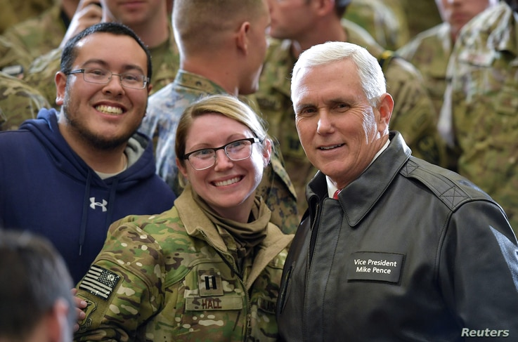 U.S. Vice President Mike Pence poses for photos with troops in a hangar at Bagram Air Field in Afghanistan, Dec. 21, 2017.