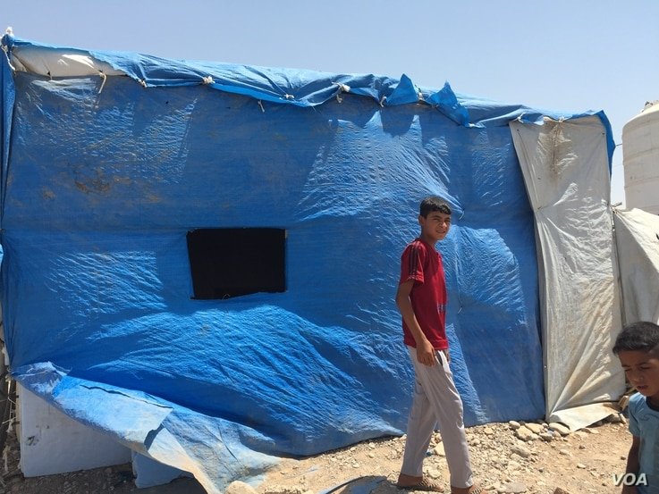 A displaced Sunni teenager walks past a blue plastic covered building in Baharka camp which houses just under 4,000 people on the outskirts of Irbil, in the Kurdistan region of Iraq, Aug, 2015 (VOA photo - Sharon Behn).