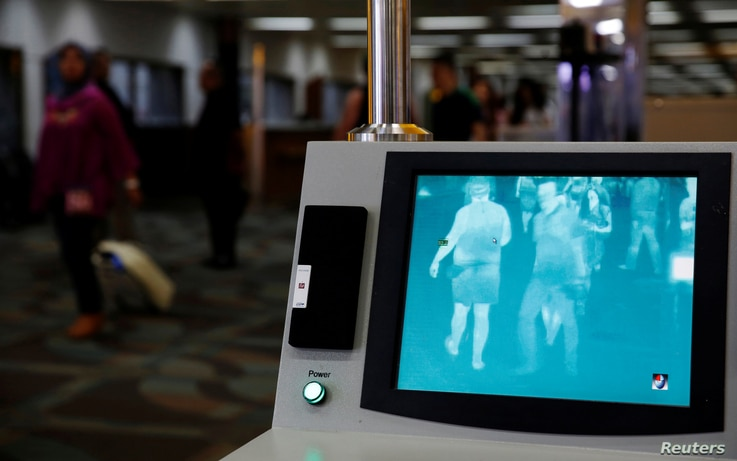 Airline passengers walk past a thermal scanner for body temperature shortly after landing from Singapore at Soekarno-Hatta airport in Jakarta, Indonesia, August 30, 2016.