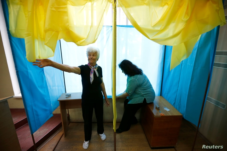 Election commission workers adjust voting booth at the poling station in Kyiv, May 24, 2014.