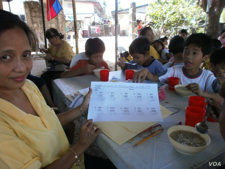 Lessons are over and a lunch of rice porridge with chicken and beans is served.  Sitting at the 10-year olds' table, volunteer teacher Yolanda Penalosa shows off her student Ericson's quick progress in arithmetic, May 25, 2012. (S. Orendain/VOA)