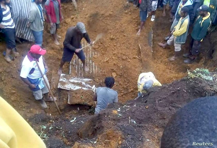 Locals dig for bodies after a house was covered by a landslide in the town of Mendi after an earthquake struck Papua New Guinea's Southern Highlands, in this image taken Feb. 27, 2018, obtained from social media.