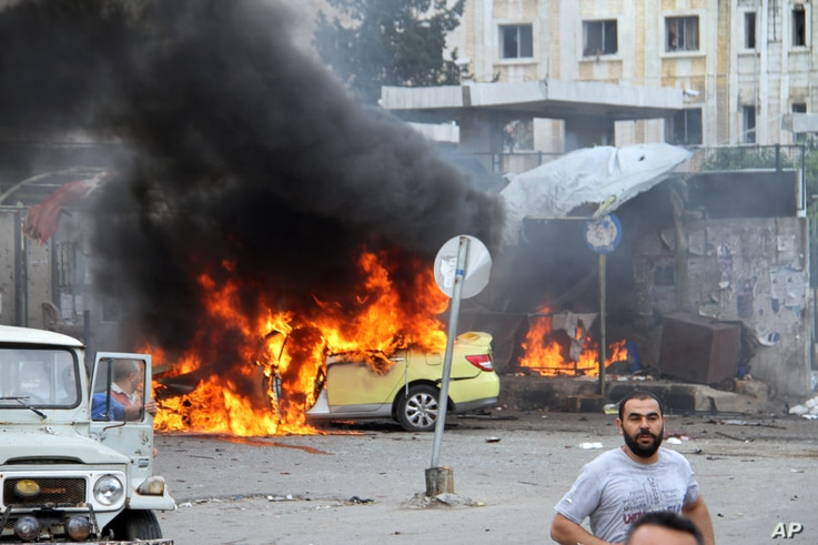 In this photo released by the Syrian official news agency SANA, Syrians gather in front of a burning car at the scene where suicide bombers blew themselves up, in the coastal town of Tartus, Syria, Monday, May 23, 2016.
