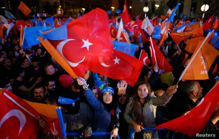 Women wave flags celebrating the AK Party's lead in Sunday's parliamentary elections outside party headquarters in Ankara, Turkey, November 1, 2015.