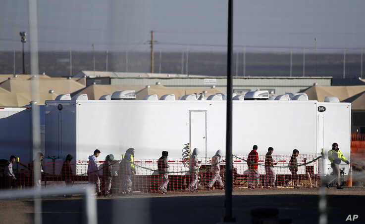 FILE - In this Dec. 13, 2018 photo, migrant teens walk in a line through the Tornillo detention camp in Tornillo, Texas. The Trump administration says it will keep the tent city holding more than 2,000 migrant teenagers open through early 2019.