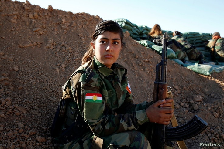 An Iranian-Kurdish female fighter holds her weapon during a battle with Islamic State militants in Bashiqa, near Mosul, Iraq, Nov. 3, 2016.