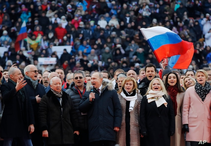 Russian President Vladimir Putin, center, and other guests sing Russia's national anthem during a massive rally in his support as a presidential candidate at the Luzhniki stadium in Moscow, March 3, 2018.