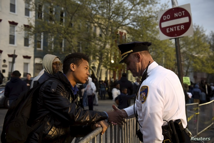 Ninth-grader Tremaine Holmes shakes hands with Captain Erik Pecha in front of the Baltimore Police Department Western District station during a protest against the death in police custody of Freddie Gray in Baltimore, April 23, 2015.