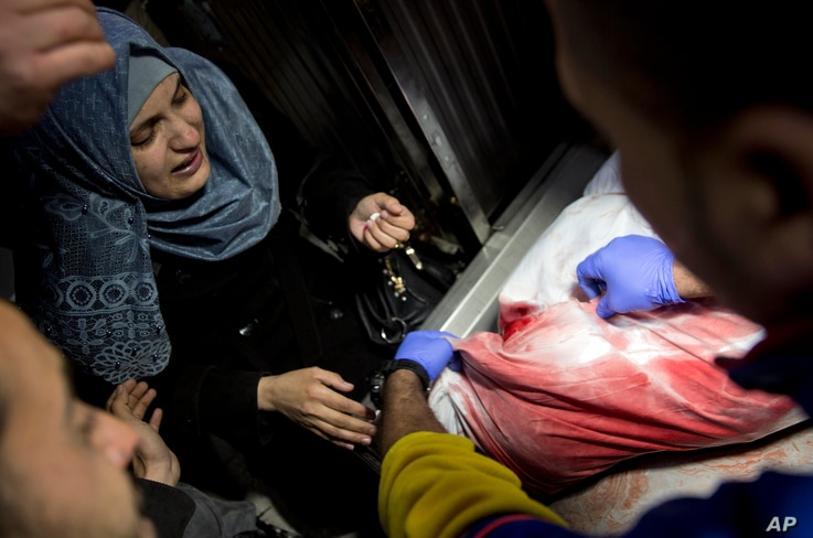 A Palestinian relative reacts after seeing the body of Adham Emara, 17, who was shot and killed by Israeli troops during a protest next to the Israeli border in the eastern Gaza Strip, in the morgue of the Shifa hospital in Gaza City, March 30, 2019....