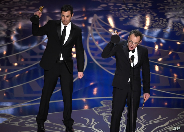 """Josh Singer, left, and Tom McCarthy accept the award for best original screenplay for """"Spotlight"""" at the Oscars on Feb. 28, 2016, at the Dolby Theatre in Los Angeles."""