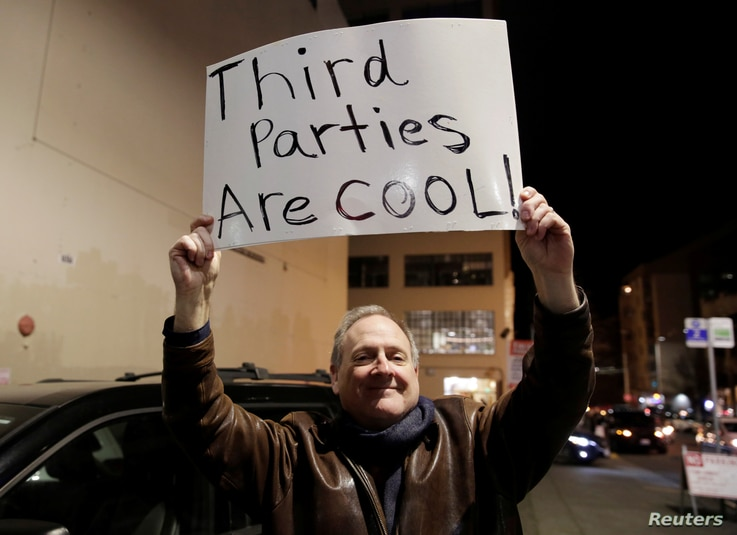 Libertarian Jeff Jared of Kirkland, Wash.,holds a sign in support of third parties before former Starbucks CEO Howard Schultz speaks during his book tour in Seattle, Jan. 31, 2019.