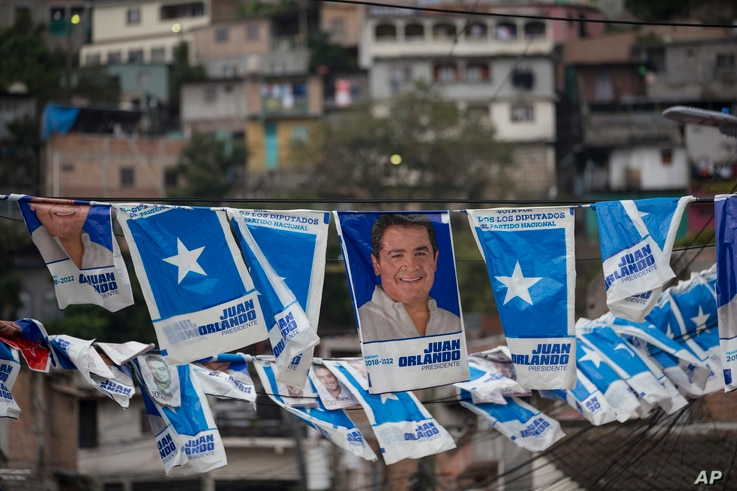Banners with a portrait of Honduran President and current presidential candidate Juan Orlando Hernandez hang outside a polling station during the general elections in Tegucigalpa, Nov. 26, 2017.
