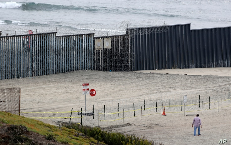 Concertina wire partially lines the border wall separating Tijuana, Mexico, behind, and San Diego, Nov. 19, 2018, in San Diego.