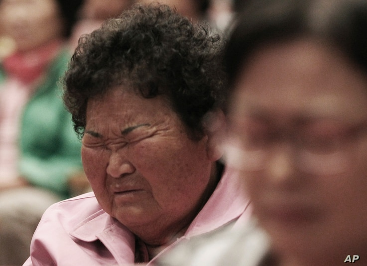 A local resident closes her eyes during a prayer to wish for safe return of passengers of the sunken ferry Sewol during an annual Easter service in Jindo, South Korea, Sunday, April 20, 2014. After more than three days of frustration and failure, div