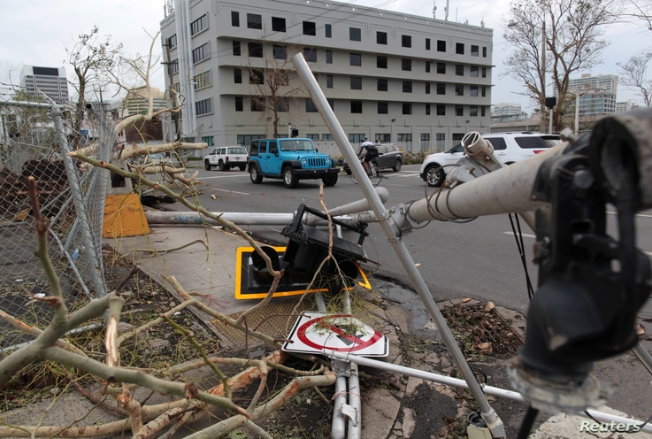 A broken traffic light, a street sign and branches lie on the street after the area was hit by Hurricane Maria, in San Juan, Puerto Rico, Sept. 22, 2017.