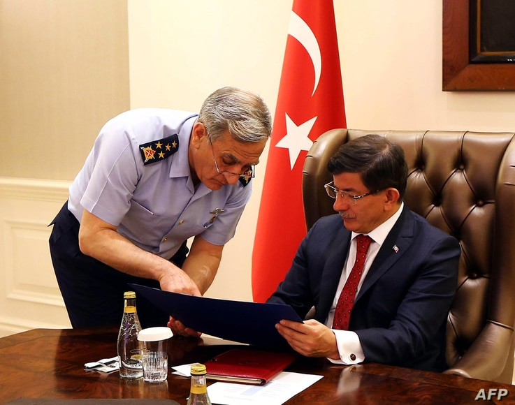 Commander of the Turkish Air Forces and Full General Akin Ozturk, left, briefs Turkey's Prime Minister Ahmet Davutoglu during a special security meeting on Islamic State in Syria and the PKK in Iraq, at Cankaya Palace, Ankara, July 25, 2015.