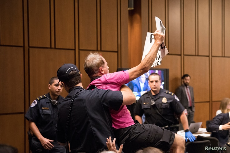 A protester is arrested as Supreme Court nominee Brett Kavanaugh testifies during the third day of his confirmation hearing before the Senate Judiciary Committee on Capitol Hill in Washington, Sept. 6, 2018.