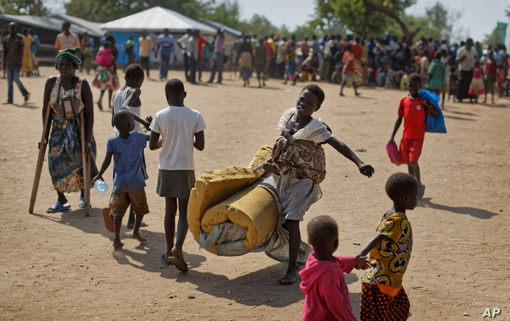 FILE - A South Sudanese refugee girl with a baby on her back carries a foam mattress, June 9, 2017, to the communal tent at the Imvepi reception center, where newly arrived refugees are processed before being allocated plots of land in nearby Bidi Bi...