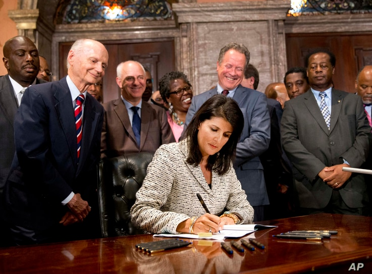 South Carolina Gov. Nikki Haley signs a bill into law as former South Carolina governors and officials look on Thursday, July 9, 2015.