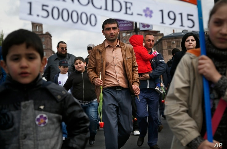 """Armenians carry a placard with a sign reading """"1915"""" and """"1500000"""", the year and numbers of victims of mass killings of Armenians by Ottoman Turks on a city street in Yerevan, Armenia, April 24, 2015."""