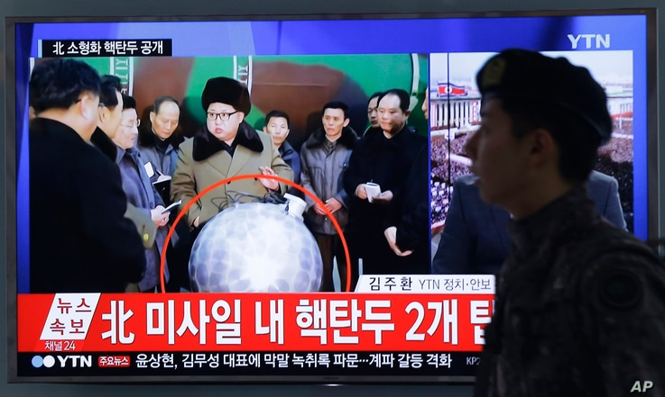 """A South Korean army soldier walks by a TV screen showing North Korean leader Kim Jong Un with superimposed letters that read: """"North Korea's nuclear warhead"""" during a news program at Seoul Railway Station in Seoul, South Korea, March 9, 2016."""