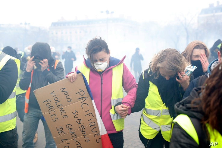 """FILE - """"Yellow vest"""" protesters run away from tear gas during clashes with riot police, in Paris, France, Jan. 12, 2019."""