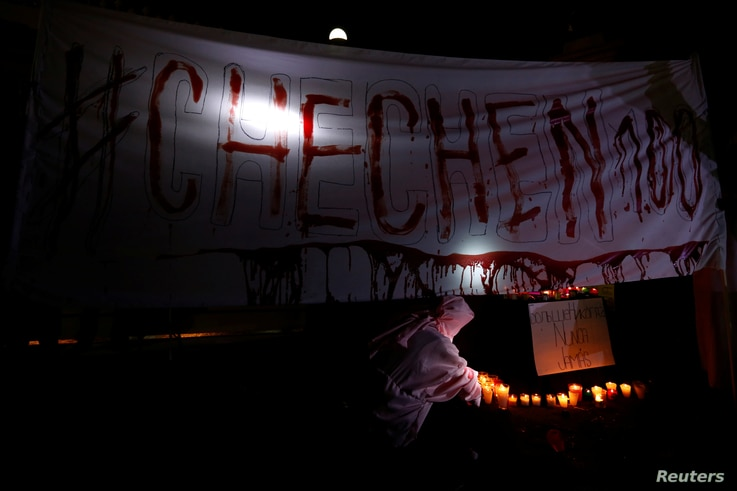 Activists from the group Chok3 paint a banner with their own blood during a protest discrimination and violence against the gay community in Chechnya and other regions of Russia, outside the Russian embassy in Mexico City, Mexico, April 20, 2017.