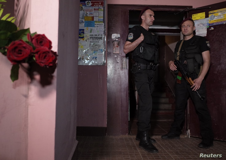 Ukrainian police officers guard as flowers are placed near the entrance to a house where Russian journalist Arkady Babchenko was shot and died of his wounds in an ambulance, in Kyiv, Ukraine, May 29, 2018.