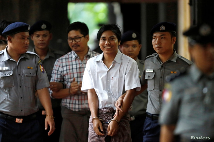 Police escort detained Reuters journalists Kyaw Soe Oo and Wa Lone as they arrive before a court hearing in Yangon, Myanmar, Aug. 20, 2018.