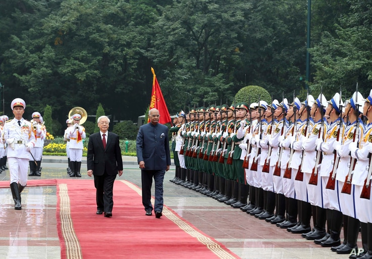 Indian President Ram Nath Kovind, right, and his Vietnamese counterpart Nguyen Phu Trong review an honor guard in Hanoi, Vietnam, Tuesday, Nov. 20, 2018.
