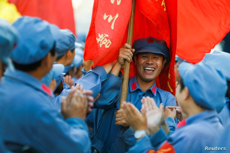 Participants dressed in replica Red Army uniforms welcome teammates as they return from a hike through the mountains during a Communist team-building course extolling the spirit of the Long March outside Jinggangshan, Jiangxi province, China, Sept. 1...