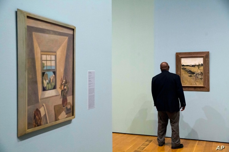 "Niles Spencer's 1927 painting ""The Dormer Window,"" left, and Andrew Wyeth's 1946 painting ""The Stone Fence"" are displayed as a security guard walks through the exhibit ""Cross Country: The Power of Place in American Art, 1915-1950,"" at the High Museum..."