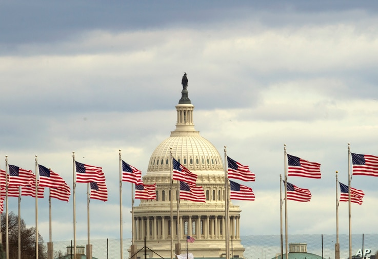 Flags fly in front of the U.S. Capitol in Washington, Tuesday morning, Jan. 1, 2019, as a partial government shutdown stretches into its third week.