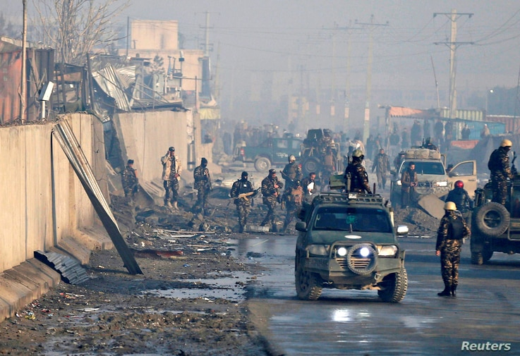 Afghan security forces inspect the site of a car bomb blast in Kabul, Afghanistan