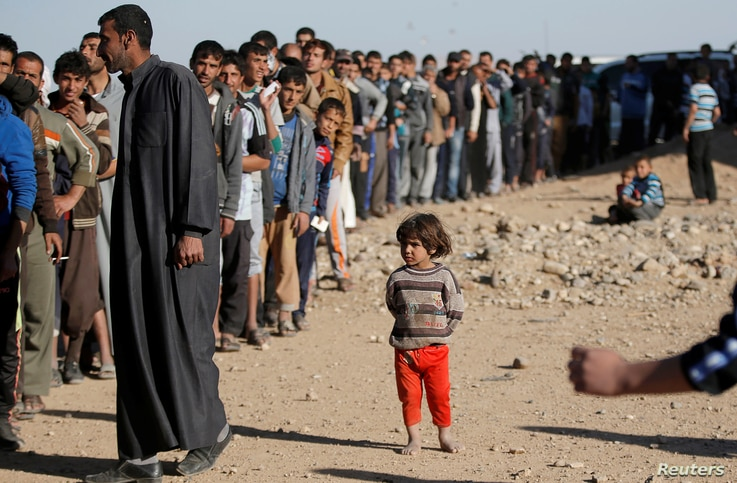 A child stands next to men who are waiting in line for food donated by an Iraqi government organisation at the outskirts of Mosul, Iraq, Nov. 20, 2016.