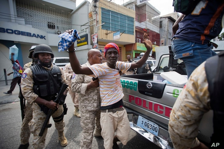A demonstrator is detained after clashes with national police during a protest against government tax hikes in Port-au-Prince, Haiti, Oct. 5, 2017.