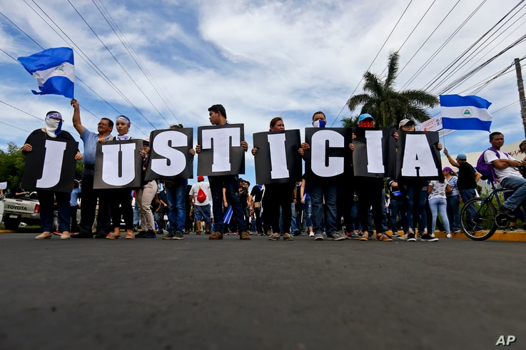"In this May 30, 2018 photo, anti-government protesters carries letters that form the Spanish word for ""Justice"" during a march against the government of Nicaragua President Daniel Ortega, and his wife Vice President Rosario Murillo in Managua, Nicara..."