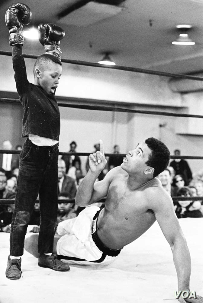 Ali & the Kid, Muhammad Ali has fun with a young child during a workout break, 1967. (George Kalinsky)