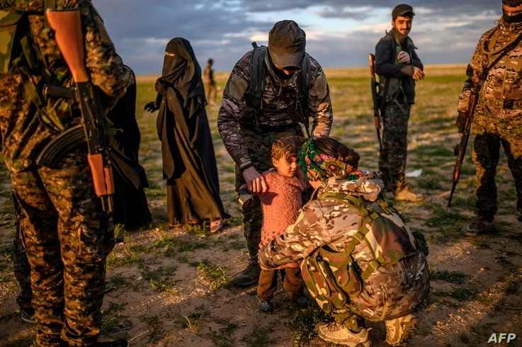 A member of the Kurdish-led Syrian Democratic Forces (SDF) holds a toddler during a security check of her and her mother after they left the IS group's last holdout of Baghuz, in Syria's northern Deir Ezzor province, Feb. 27, 2019.