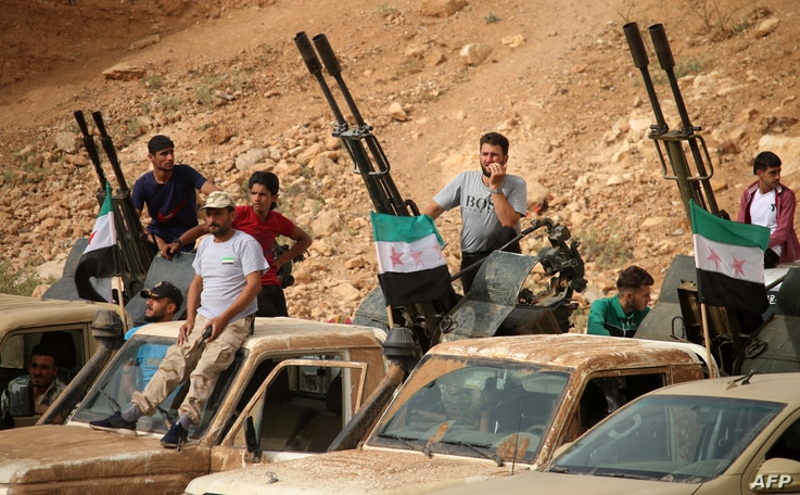 Syrian rebel fighters man anti-aircraft guns mounted in the back of pickup trucks during a military parade near the southern city of Daraa on June 7, 2018.