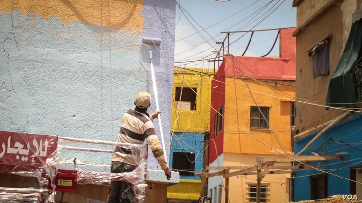 A man prepares another wall for painting in the art-lined neighbourhood has been named Ouzville. (J. Owens for VOA)