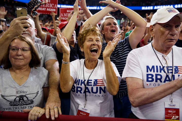 Supporters of President Donald Trump, wearing Mike Braun for Congress shirts, cheer as he arrives for a campaign rally at the Ford Center in Evansville, Ind.