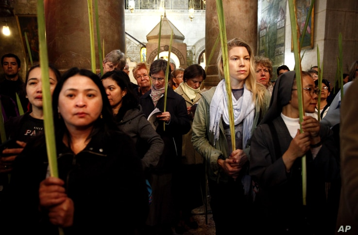 Christian pilgrims hold palm fronds during the Palm Sunday procession in the Church of the Holy Sepulcher, traditionally believed by many to be the site of the crucifixion, in Jerusalem's Old City, Sunday, March 20, 2016.